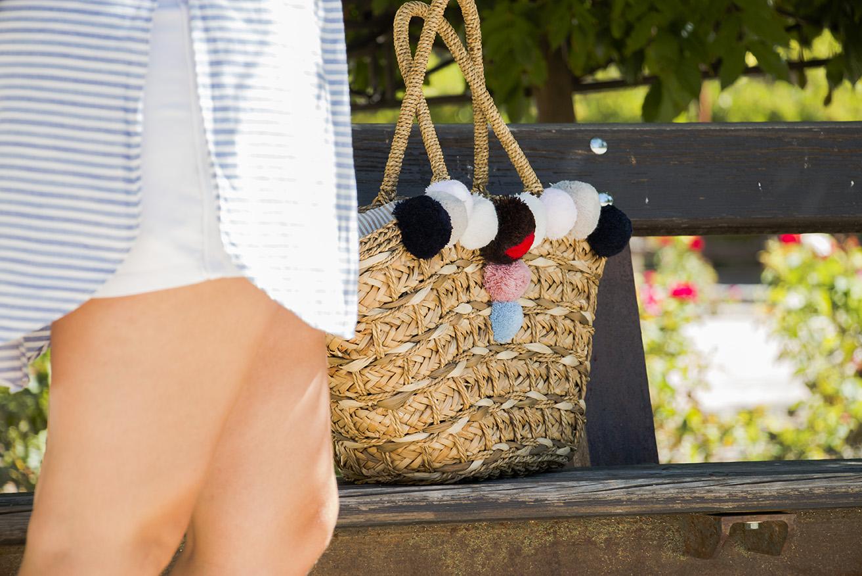 bolso de rafia con pompones y camisa de rayas azul