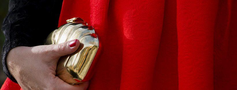 Look navideño vestido rojo, detalle tela y bolso dorado